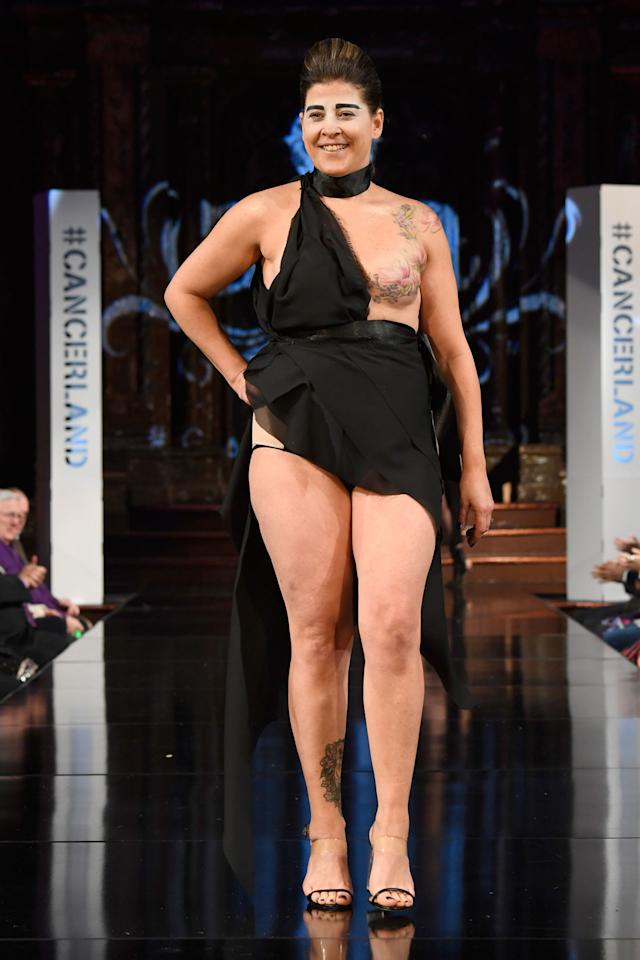 <p>Model wears a one shoulder dress to show off one breast that is covered in a floral pink tattoo at the AnaOno x #Cancerland show during NYFW. (Photo: Getty) </p>