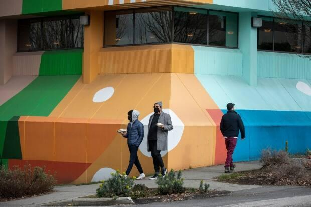People in masks walk in front of a mural on the side of Hootsuite's offices in Vancouver on March 2, 2021.  (Ben Nelms/CBC - image credit)