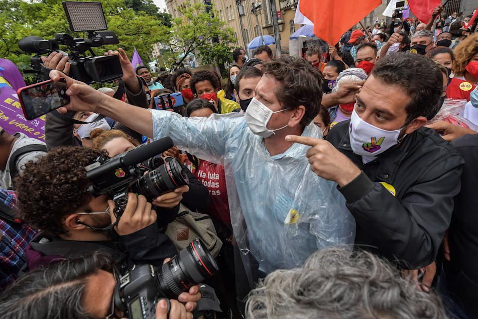 Sao Paulo's mayoral candidate for the Socialism and Freedom Party (PSOL), Guilherme Boulos (R), campaigns along with defeated candidates Jilmar Tatto (C) of the Workers' Party (PT) and Orlando Silva (out of frame), of the Communist Party of Brazil (PCdoB), during a rally in Sao Paulo downtown, Brazil, on November 18, 2020. - The Brazilian municipal runoff election will take place on November 29. Left-wing candidate Guilherme Boulos won on November 15 a surprise pass to the second round, where he will face current Mayor Bruno Covas. (Photo by Nelson ALMEIDA / AFP) (Photo by NELSON ALMEIDA/AFP via Getty Images)