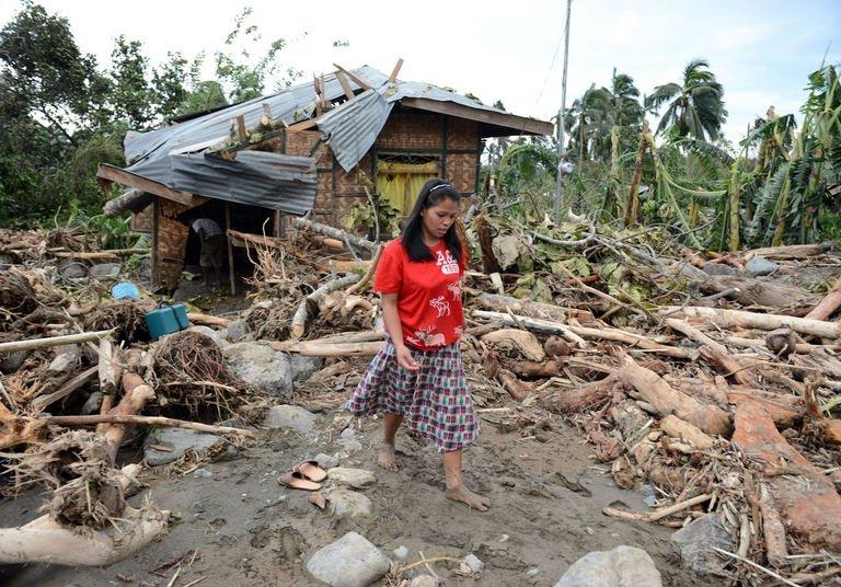 A woman walks amongst debris next to her damaged house in the village of Andap. At least 274 people have been killed and hundreds remain missing in the Philippines from the deadliest typhoon to hit the country this year, according to the civil defence chief