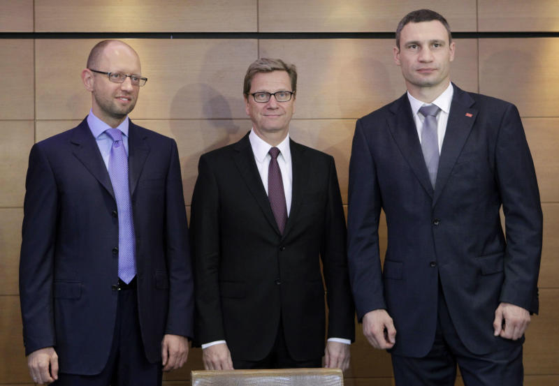 Ukrainian opposition leader Arseniy Yatsenyuk, left, and Ukrainian opposition party Udar (Punch) chairman and WBC heavyweight champion Vitali Klitschko, right, pose with German Foreign Minister Guido Westerwelle for photographers in Kiev, Ukraine, Friday, June 21, 2013. Yatsenyuk asked Westerwelle Friday to help send jailed former Ukrainian Prime Minister Yulia Tymoshenko to Germany. (AP Photo/Sergei Chuzavkov)