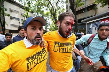 Juan Requesens (C), deputy of the Venezuelan coalition of opposition parties (MUD), is helped after been injured during clashes with pro-government supporters outside the offices of the Venezuela's ombudsman in Caracas, Venezuela April 3, 2017. REUTERS/Carlos Garcia Rawlins