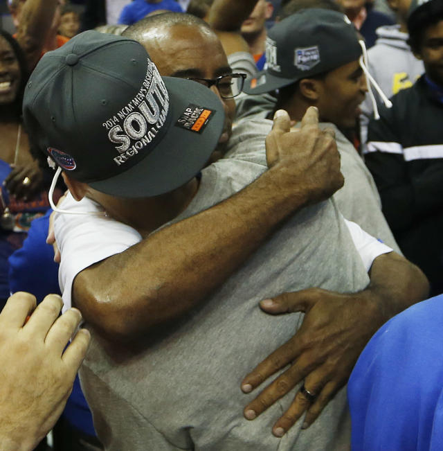 Florida forward Will Yeguete (15) embraces a person after the second half in a regional final game against Dayton at the NCAA college basketball tournament, Saturday, March 29, 2014, in Memphis, Tenn. Florida won 62-52. (AP Photo/John Bazemore)