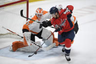 Philadelphia Flyers goaltender Brian Elliott (37) tracks the puck as Washington Capitals right wing Garnet Hathaway (21) tries for a shot during the first period of an NHL hockey game Tuesday, April 13, 2021, in Washington. (AP Photo/Nick Wass)
