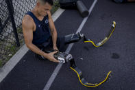 Luis Puertas fixes his prosthetic blades on his residual limbs during one of his daily training sessions in a sports complex in Orlando, Fla., on Monday, Aug. 9, 2021. Puertas, 34, lost both his legs in September 2006 as he patrolled a crowded Baghdad neighborhood. His legs were severed when a massive IED blasted through his armored vehicle. (AP Photo/Emilio Morenatti)