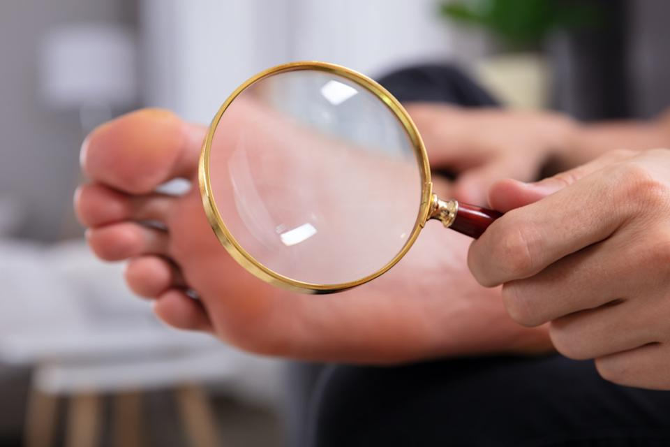 Man's Hand Holding Magnifying Glass In Front Of His Feet