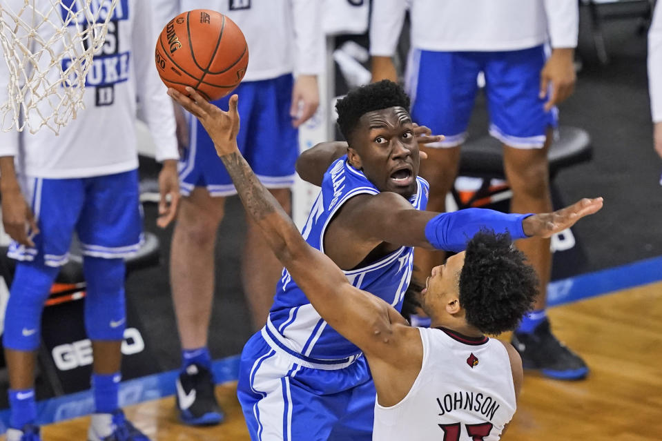 Duke center Mark Williams (15) tries to block the shot of Louisville guard David Johnson (13) during the first half of an NCAA college basketball game in the second round of the Atlantic Coast Conference tournament in Greensboro, N.C., Wednesday, March 10, 2021. (AP Photo/Gerry Broome)