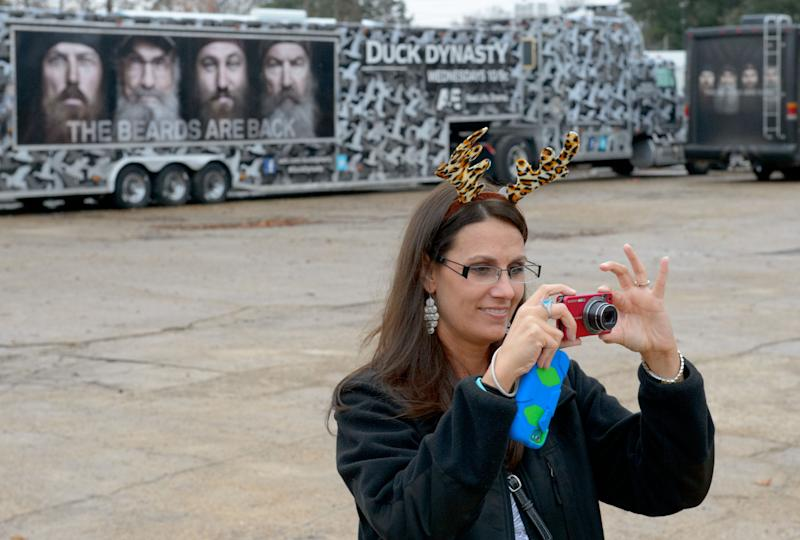 """This Dec. 21, 2013 photo shows Trish Singlteon, of Durant, Okla., taking a picture of her family outside the Duck Commander store in West Monroe, La. The town is the setting for the popular """"Duck Dynasty""""series, where show patriarch, Phil Robertson, was suspended last week for disparaging comments he made to GQ magazine about gay people. (AP Photo/Matthew Hinton)"""