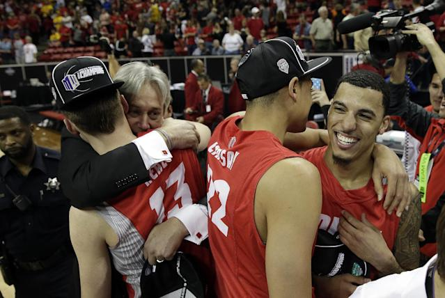New Mexico head coach Craig Neal celebrates with his players Cullen Neal, left, Merv Lindsay and Kendall Williams after winning an NCAA college basketball game against San Diego State for the Mountain West Conference tournament championship on Saturday, March 15, 2014, in Las Vegas. New Mexico defeated San Diego State 64-58. (AP Photo/Isaac Brekken)