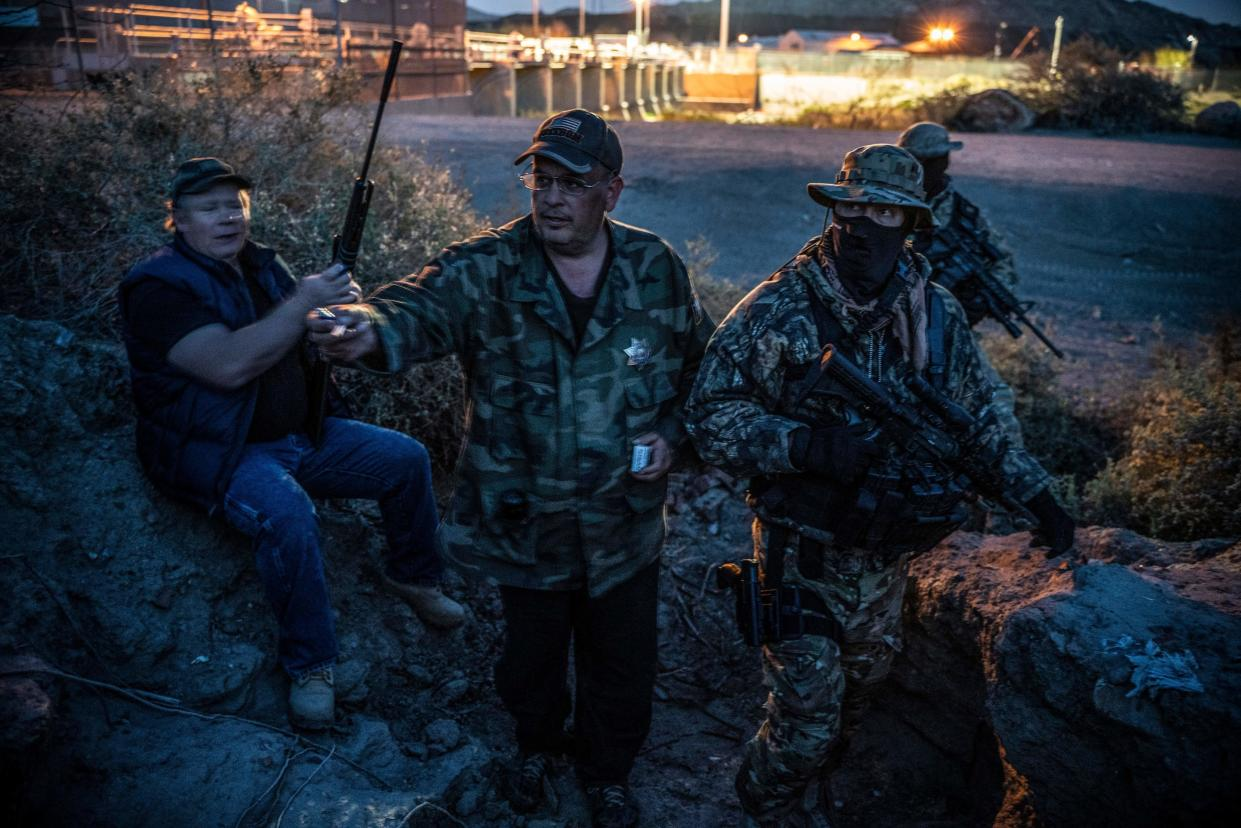 """United Constitutional Patriots members Jeff Allen, Jim Benvie, """"Viper"""" and """"Stinger"""" take a cigarette break while patrolling the U.S.-Mexico border in Sunland Park, New Mexico, last month. (PAUL RATJE via Getty Images)"""