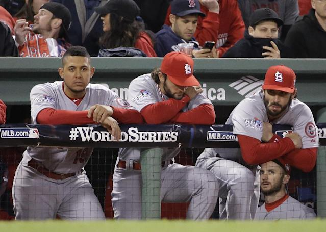 St. Louis Cardinals from left, Jon Jay, Pete Kozma and Matt Carpenter watch from the dugout during the ninth inning of Game 1 of baseball's World Series against the Boston Red Sox Wednesday, Oct. 23, 2013, in Boston. The Red Sox won 8-1. (AP Photo/David J. Phillip)