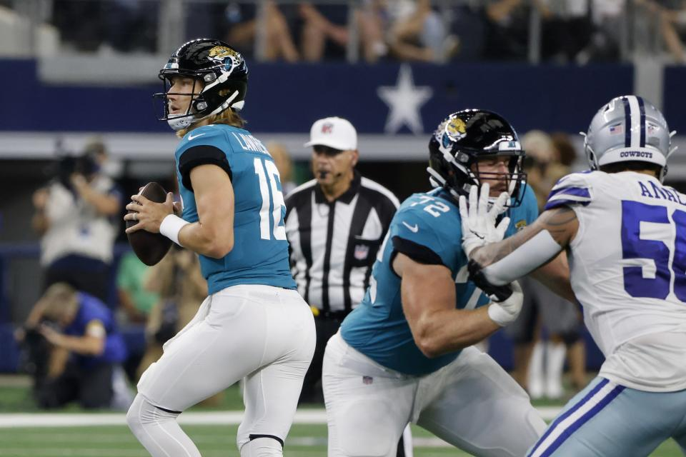 Jacksonville Jaguars quarterback Trevor Lawrence (16) drops back to throw a pass as offensive tackle Walker Little (72) defends against pressure from Dallas Cowboys defensive end Bradlee Anae (56) in the first half of a preseason NFL football game in Arlington, Texas, Sunday, Aug. 29, 2021. (AP Photo/Michael Ainsworth)
