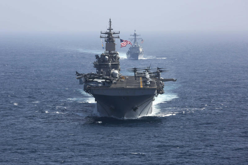 "CORRECTS DATE - In this Friday, May 17, 2019, photo released by the U.S. Navy, the amphibious assault ship USS Kearsarge and the Arleigh Burke-class guided-missile destroyer USS Bainbridge sail in formation as part of the USS Abraham Lincoln aircraft carrier strike group in the Arabian Sea. Commercial airliners flying over the Persian Gulf risk being targeted by ""miscalculation or misidentification"" from the Iranian military amid heightened tensions between the Islamic Republic and the U.S., American diplomats warned Saturday, May 18, 2019, even as both Washington and Tehran say they don't seek war. (Mass Communication Specialist 1st Class Brian M. Wilbur, U.S. Navy via AP)"
