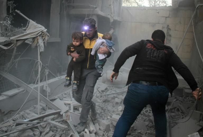 A Syrian man carries two children following regime air strikes on the rebel-held town of Douma on February 7, 2018