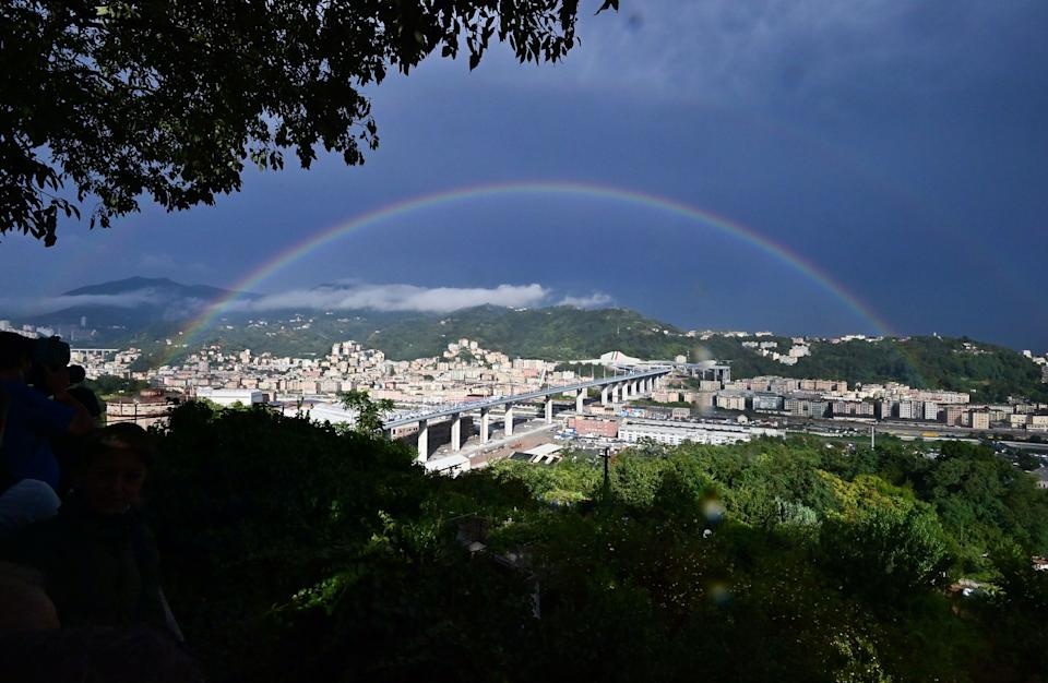 TOPSHOT - A rainbow is seen over the new San Giorgio bridge on the inauguration day on August 3 , 2020 in Genoa, the new high-tech structure will have four maintenance robots running along its length to spot weathering or erosion, as well as a special dehumidification system to limit corrosion. - Italy inaugurates a sleek new bridge in Genoa, though relatives of the 43 people killed when the old viaduct collapsed say the pomp and ceremony risk overshadowing the tragedy. (Photo by MIGUEL MEDINA / AFP) (Photo by MIGUEL MEDINA/AFP via Getty Images) (Photo: MIGUEL MEDINA via Getty Images)