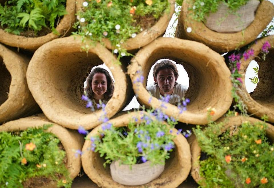 Designers Finbar Ward and Tilly Dallas look through bee hives formed from cylinders of clay, as part of RHS Chelsea Flower Show (Yui Mok/PA) (PA Wire)