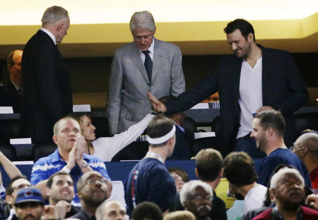 From left, Dallas Cowboys owner Jerry Jones, former president Bill Clinton, and Cowboys quarterback Tony Romo take their seats to watch Connecticut and Kentucky during the first half of the NCAA Final Four tournament college basketball championship game Monday, April 7, 2014, in Arlington, Texas. (AP Photo/David J. Phillip)