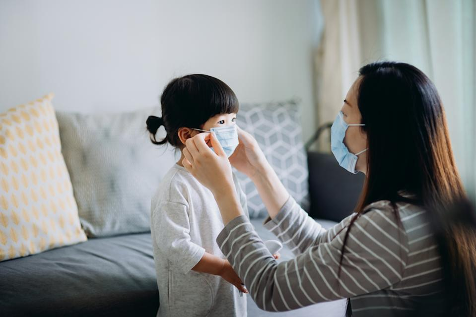 Young Asian mother putting on surgical mask for little daughter before heading out to prevent the spread of cold and flu and viruses