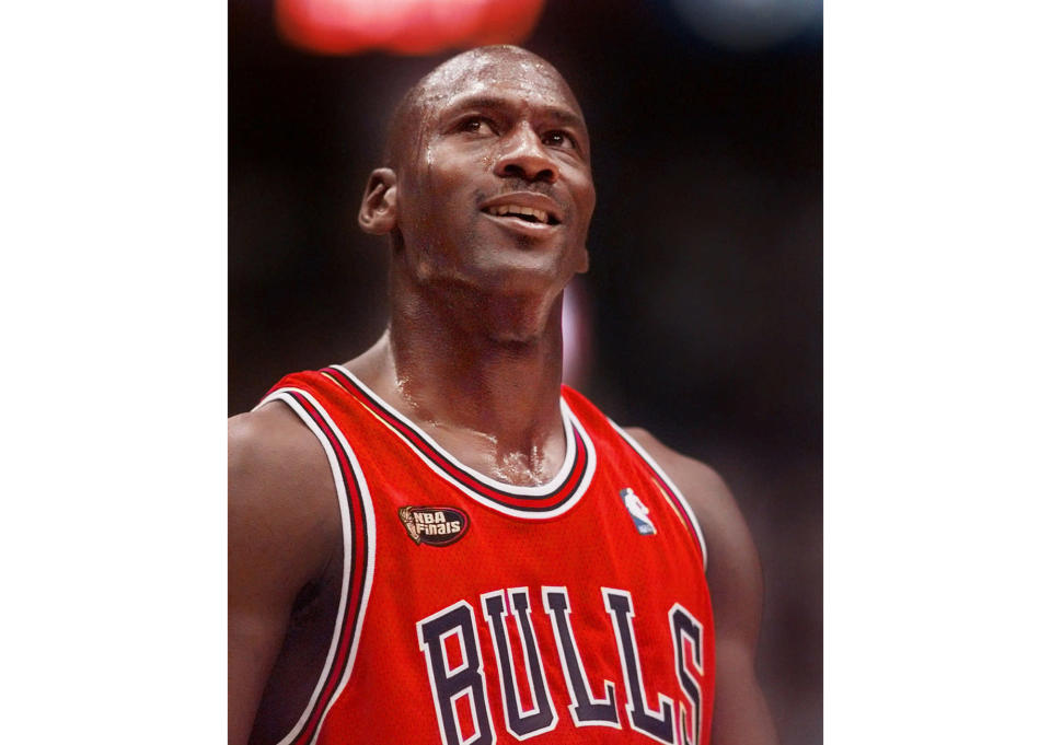 """FILE -This June 14, 1998 file photo shows Chicago Bulls' Michael Jordan looking up at the score during the third quarter of their NBA Finals game against the Utah Jazz in Salt Lake City. """"The Last Dance,"""" ESPN's docuseries detailing the 1998 and final season of the Chicago Bulls championship dynasty, has served as a reminder to basketball fans of the greatness of Michael Jordan on the court. It also shed light on his worldwide marketing allure. (AP Photo/Mark J. Terrill, File)"""