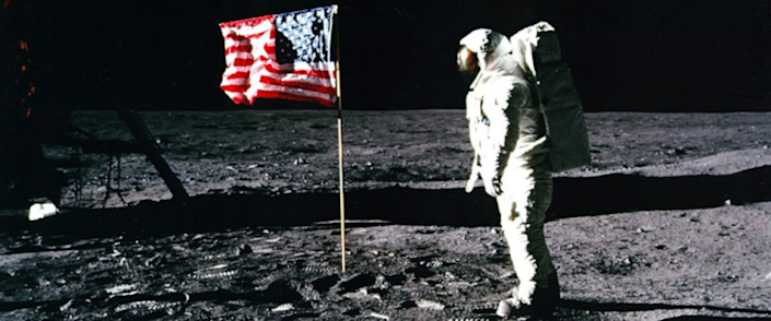 astronaut near the american flag that's just been planted on the moon