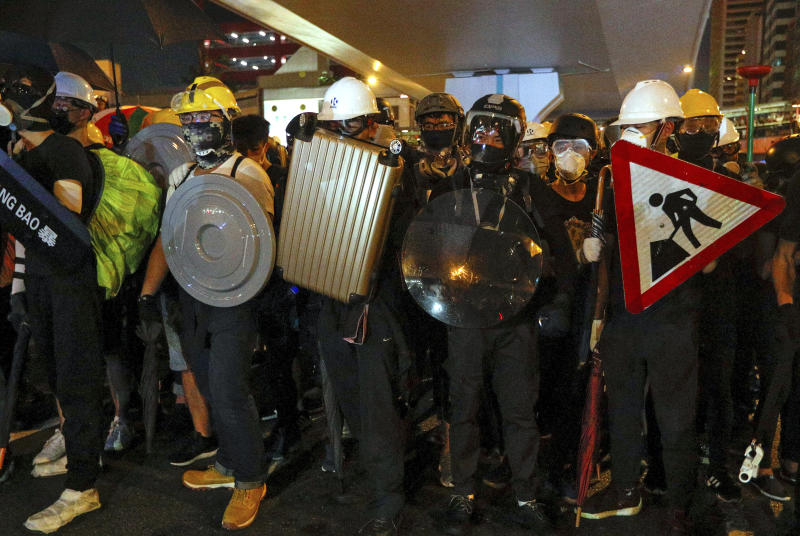 Protesters carrying home-made shields face off with riot policemen on a street in Hong Kong, Sunday, July 21, 2019. Hong Kong police have thrown tear gas canisters at protesters after they refused to disperse. Hundreds of thousands of people took part in a march Sunday to call for direct elections and an independent investigation into police tactics used during earlier pro-democracy demonstrations. Police waved a black warning flag Sunday night before lobbing the canisters into a crowd of protesters. (AP Photo/Bobby Yip)
