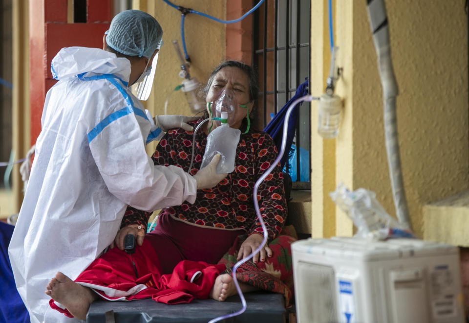 A paramedic attends to a COVID-19 patient outside an emergency ward of a government run hospital in Kathmandu, Nepal, Wednesday, May 12, 2021. (AP Photo/Niranjan Shrestha)
