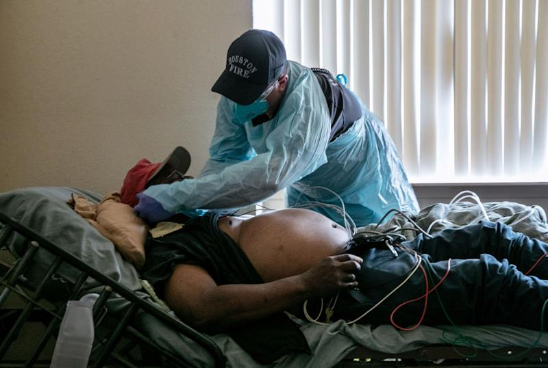 A medic with the Houston Fire Department adjusts a mask on a patient with Covid-19 symptoms before transporting him to a hospital. Source: Getty