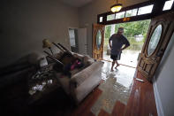 Danny Gonzales, walks in his flooded house as water recedes, after Tropical Storm Claudette passed through, in Slidell, La., Saturday, June 19, 2021. The National Hurricane Center declared Claudette organized enough to qualify as a named storm early Saturday, well after the storm's center of circulation had come ashore southwest of New Orleans.(AP Photo/Gerald Herbert)