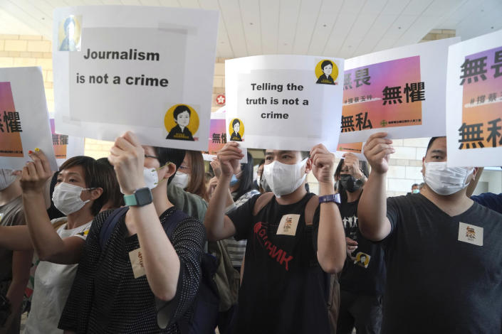 Supporters of Hong Kong journalist Choy Yuk-ling, chant placards outside a court in Hong Kong Thursday, April 22, 2021. A Hong Kong journalist was fined 6,000 Hong Kong dollars ($775) on Thursday after being found guilty of making false statements while obtaining information from a vehicle database, in the latest blow to press freedom in the city as authorities continue their crackdown on dissent. (AP Photo/Kin Cheung)