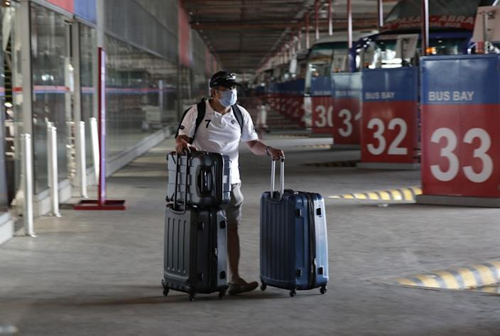 A Filipino seafarer pushes his bag at a bus terminal as he waits for a free bus ride in Paranaque, Metro Manila, Philippines, after spending weeks quarantined on a ship, Thursday May 28 2020. Seafarers were given a free ride to their provinces as the government continues to ease the lockdown which was set to prevent the spread of the new coronavirus in the country. (AP Photo/Aaron Favila)