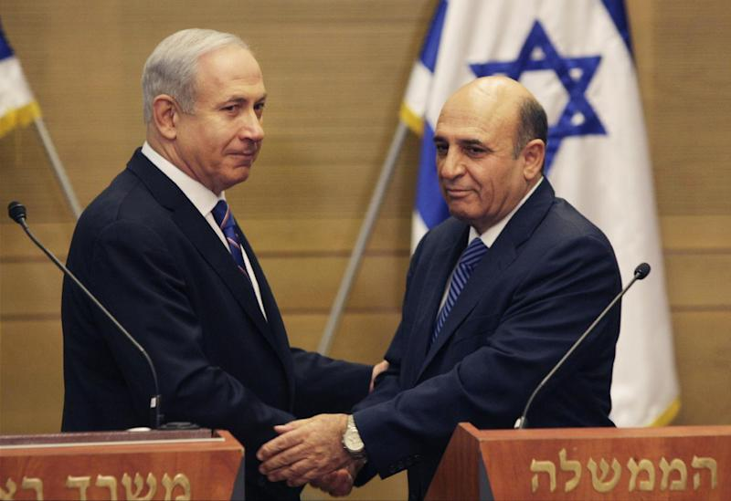 """Israel's Prime Minister Benjamin Netanyahu, left, and Kadima party leader Shaul Mofaz shake hands before holding a joint press conference announcing the new coalition government, in Jerusalem, Tuesday, May 8, 2012. Netanyahu said Tuesday his new coalition government will promote a """"responsible"""" peace process with the Palestinians. (AP Photo/Sebastian Scheiner)"""