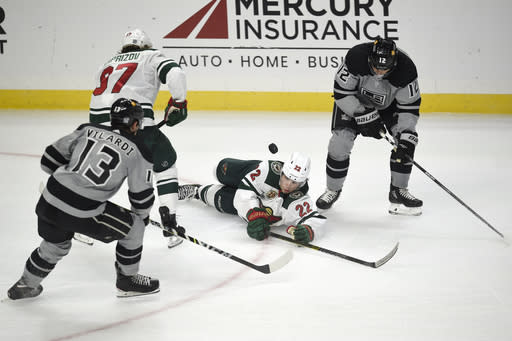 Minnesota Wild left wing Kevin Fiala, center, falls to the ice while battling for the puck with Los Angeles Kings center Trevor Moore, right, as Kings center Gabriel Vilardi, front left, and Wild left wing Kirill Kaprizov look on during the second period of an NHL hockey game in Los Angeles, Saturday, Jan. 16, 2021. (AP Photo/Kelvin Kuo)