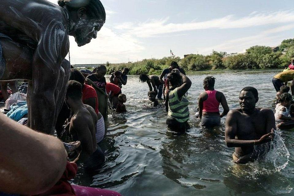 Migrants seeking asylum in the US bathe in the Rio Grande river near the International Bridge between Mexico and the US, where they wait to be processed, in Del Rio, Texas, on 16 September 2021
