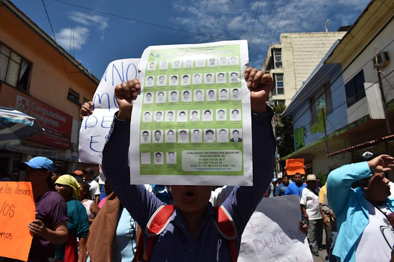 A man holds a poster with the portraits of missing students during a protest to demand justice and an explanation about the whereabouts of the students, in Chilpancingo, Guerrero state, Mexico on October 2, 2014 (AFP Photo/Yuri Cortez)