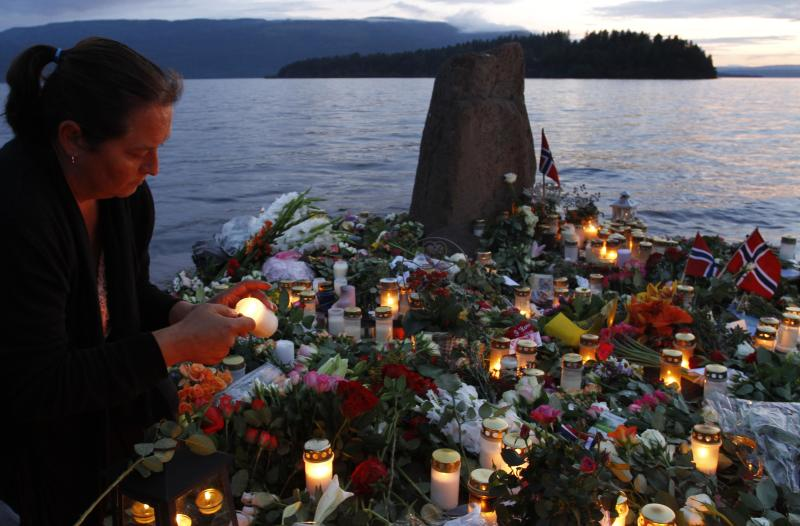A woman lights a candle in front of the Utoya island in Utvica near Sundvollen near Oslo, Norway, Tuesday, July 26, 2011, in memory of the eight people killed in Friday's blast in Oslo and the 68 who died in the shooting at the youth camp on Utoya.  (AP Photo/Ferdinand Ostrop)