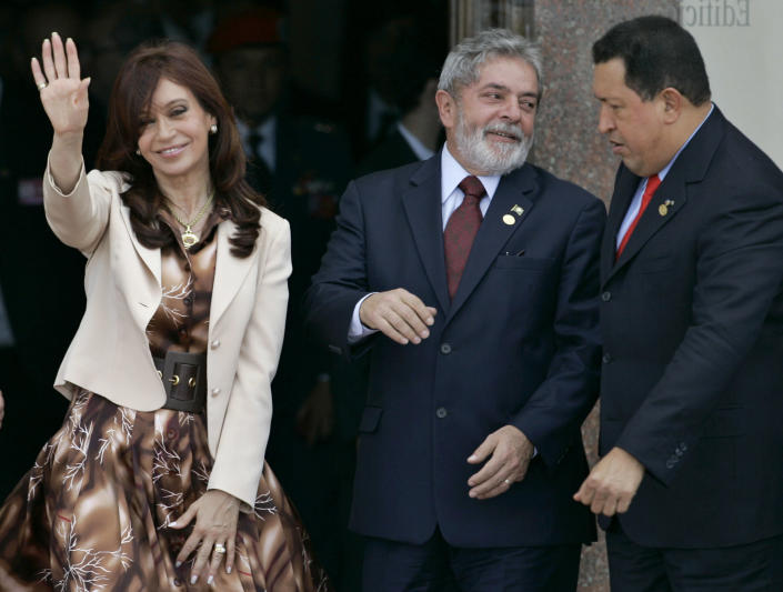 FILE - In this Dec. 18, 2007 file photo, Argentina's President Cristina Fernandez, left, waves to photographers as Brazil's President Luiz Inacio Lula da Silva, center, talks to Venezuela's President Hugo Chavez during the official photo at the Mercosur Summit in Montevideo, Uruguay. Already the Western Hemisphere's longest-serving president, Chavez has helped lead the charge of incumbents who have secured constitutional changes and stayed on for multiple terms, overturning provisions that had barred or limited re-election. Presidents in Argentina, Bolivia, Brazil and Colombia have won re-election since 2006. (AP Photo/Marcelo Hernandez, File)