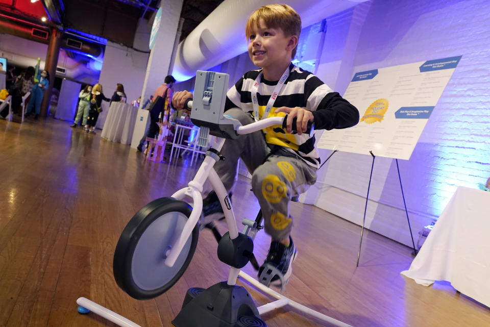 """Fox Messitt, from """"Fuller House,"""" tries out a Pelican Explore & Fit Cycle, by Little Tikes, at the TTPM Holiday Showcase, in New York, Thursday, Sept. 23, 2021. With three months until Christmas, toy companies are racing to get their toys onto store shelves as they face a severe supply network crunch. Toy makers are feverishly trying to find containers to ship their goods while searching for new alternative routes and ports. (AP Photo/Richard Drew)"""