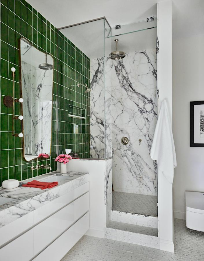 For the primary bath, Schuster chose Calacatta Paonazzo marble from ABC Stone and custom-glazed ceramic tiles from Artistic Tile. The mirror is a vintage Italian piece found at 1stDibs, and the wall sconce is from Apparatus Studio.
