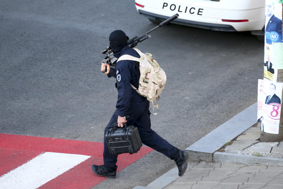 "A Georgian police sniper carries his rifle on a position near a bank where an armed assailant took several people hostage in the town of Zugdidi in western Georgia, Wednesday, Oct. 21, 2020. An armed assailant took several people hostage at a bank in the ex-Soviet nation of Georgia on Wednesday, authorities said. The Georgian Interior Ministry didn't immediately say how many people have been taken hostage in the town of Zugdidi in western Georgia, or what demands the assailant has made. Police sealed off the area and launched an operation ""to neutralize the assailant,"" the ministry said in a statement. (AP Photo/Zurab Tsertsvadze)"