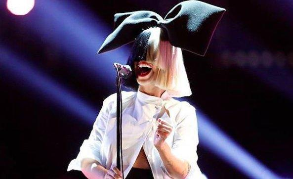 Sia singing into a microphone, wearing a wig covering her face with a oversize bow on top