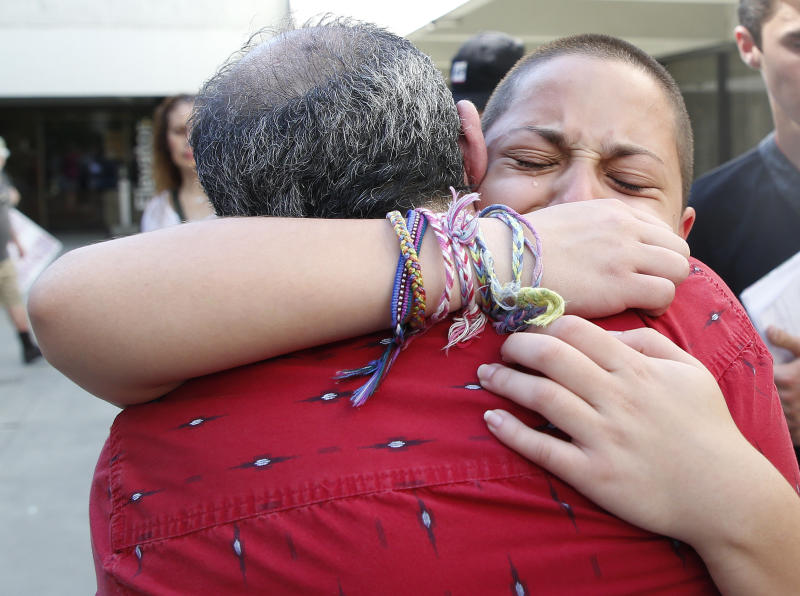 Marjory Stoneman Douglas High School student Emma González hugs her father Jose after speaking at a rally for gun control at the Broward County Federal Courthouse in Fort Lauderdale, Florida on Feb. 17, 2018. (RHONA WISE via Getty Images)