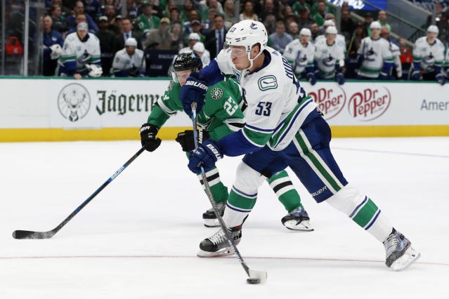 Vancouver Canucks center Bo Horvat (53) takes a shot as Dallas Stars defenseman Esa Lindell (23) looks on in the second period of an NHL hockey game in Dallas, Tuesday, Nov. 19, 2019. Horvat scored on the shot. (AP Photo/Tony Gutierrez)