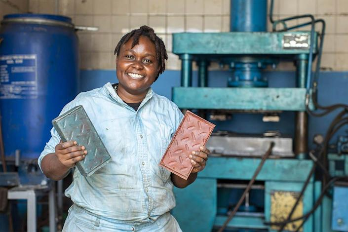 Nzambi Matee proudly holds up a pair of her super-sturdy recycled bricks.