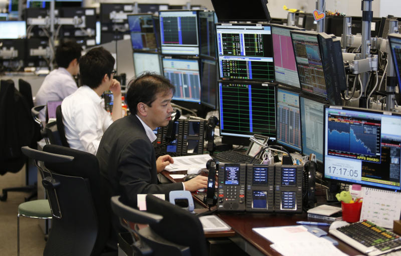 In this Wednesday, June 5, 2013 photo, Takashi Yamada, right, a government-bond trader at major brokerage Daiwa Securities Co., monitors screens at his bond trading section in Tokyo. Until a couple of months ago, Yamada had one of the most genteel jobs in Japan. Now, his days are so harried he doesn't have time to eat lunch. Shock-and-Awe monetary policies, announced in April, have sent Japanese government bonds, this nation's equivalent of U.S. Treasurys, into a whirl of volatility. (AP Photo/Shuji Kajiyama)