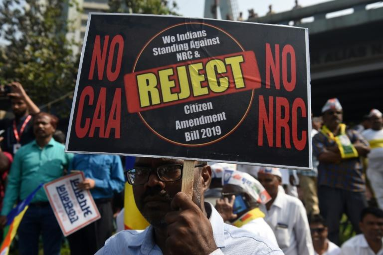 A protester holds a placard during a demonstration against India's new citizenship law in Mumbai (AFP Photo/INDRANIL MUKHERJEE        )