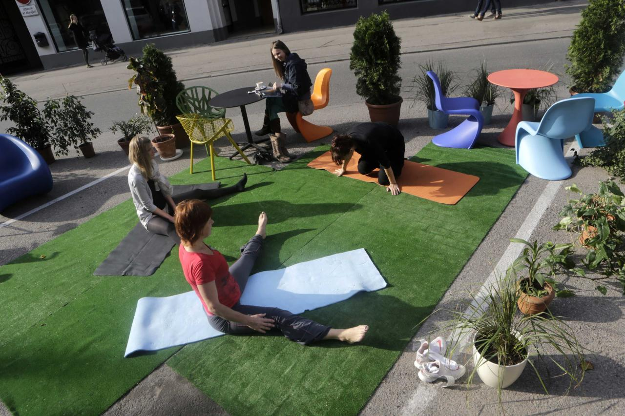 People practice yoga during the PARK(ing) Day event in Riga, September 20, 2013. The event aims to transform metered parking spaces into temporary public places to call attention to the need for more urban open spaces and discuss the creation and allocation of public spaces, according to organizers. REUTERS/Ints Kalnins (LATVIA - Tags: SOCIETY)