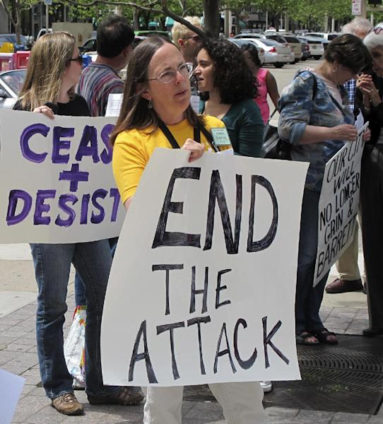 Protesters shown on Wednesday, May 8, 2013, in downtown Cincinnati. The group of 150 protesters are demanding that insurance giant Western & Southern Financial Group end a two-year court fight to stop the women's home from renovating and ultimately get them to sell the property to make way for a boutique hotel. (AP Photo/Amanda Lee Myers)