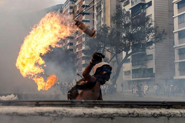 <p>An opposition demonstrator throws a Molotov cocktail at riot police during a protest against Venezuelan President Nicolas Maduro, in Caracas on May 3, 2017. (Photo: FEDERICO PARRA/AFP/Getty Images) </p>