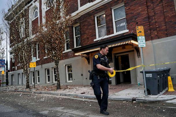PHOTO: Salt Lake City Police Office Henry Vadnais strings up police tape around fallen bricks outside a building after an earthquake in Salt Lake City on Wednesday, March 18, 2020. (Spenser Heaps/The Deseret News via AP)