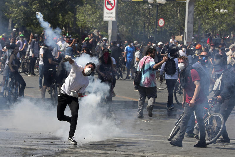 A protester returns a tear gas canister to police during clashes in Santiago, Chile, Sunday, Oct. 20, 2019. Protests in the country have spilled over into a new day, even after President Sebastian Pinera cancelled the subway fare hike that prompted massive and violent demonstrations. (Photo: Esteban Felix/AP)